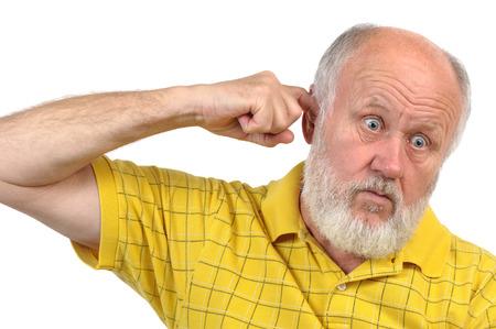 goofy bald senior man picking his ear with index finger photo