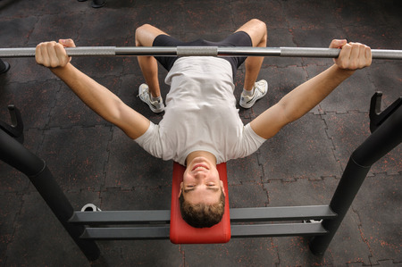 pectoral: handsome young man doing bench press workout in gym