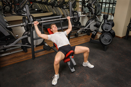 incline: Handsome young man doing Barbell Incline Bench Press workout in gym Stock Photo