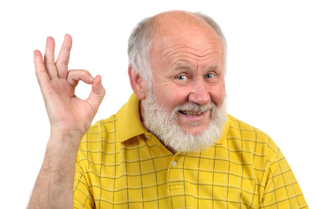 senior funny bald man in yellow t-shirt is shows gestures and grimaces photo