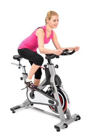 회 전자에 실내 자전거 타기 운동을 하 고 젊은 여자