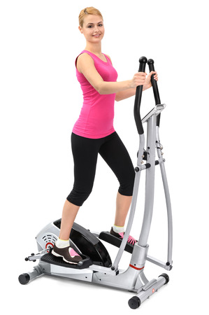 elliptical: young woman doing exercises with elliptical trainer, on white background