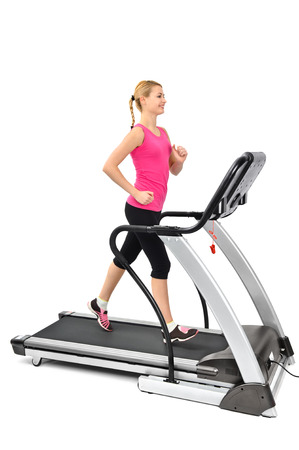 young woman doing exercises on treadmill, isolated, motion blur on moving parts photo