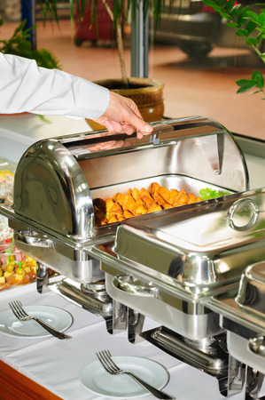 chafing dish: chafing dish heater filled with ready grilled meat inside