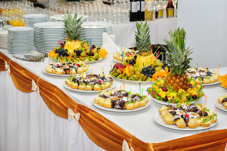 richly: Richly served banquet dessert table with fruits and cakes Stock Photo