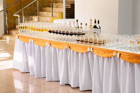banquet table with alcohol drinks and rows of stemware photo