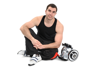 man legs: young man posing with dumbbell sitting on floor, on white background