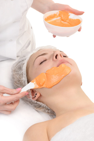 face off: Beauty salon, applying of Alginate Peel-Off Powder facial Mask Stock Photo