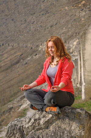 young beautiful woman doing meditation in mountains photo