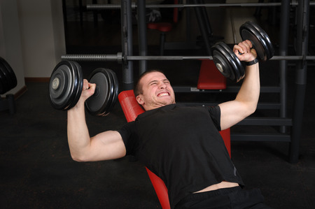 Handsome young man doing Dumbbell Incline Bench Press workout in gym photo