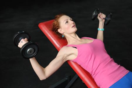 Jong meisje doet Dumbbell Incline Bench Press workout in de fitnessruimte Stockfoto