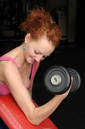 red haired girl: Giovane sottile dai capelli rossi ragazza facendo bicipiti allenamento con manubri