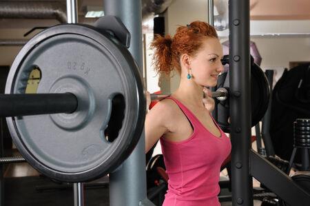 red haired girl: giovane ragazza dai capelli rosso facendo squat con bilanciere sulla macchina smith