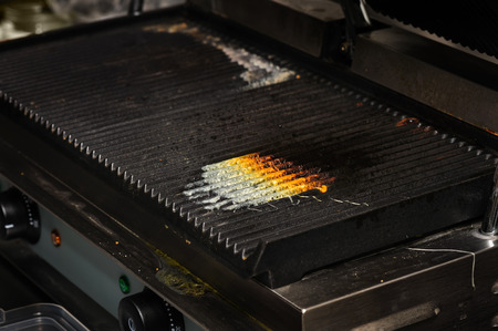 commercial equipment: dirty electrical grill in real industrial kitchen