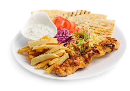 one portion of french fries, chicken kebab, salad and roasted pita photo