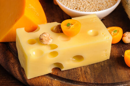 various cheeses with nuts and fruits on wooden plate Stock Photo