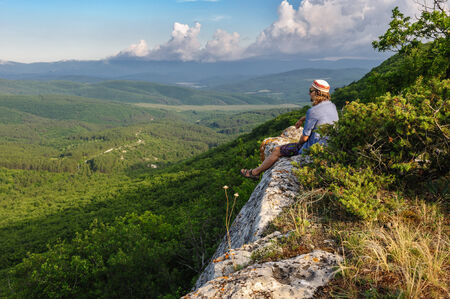 Young hiking man in the rays of sunset, standing at the top of Tope Kermen, Crimea, Ukraine or Russia photo