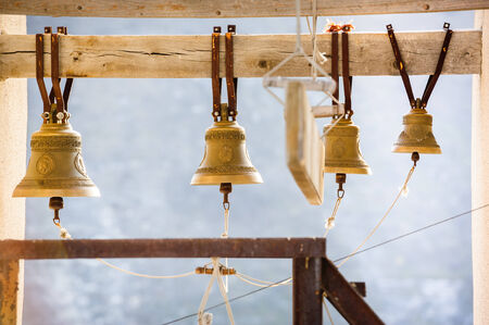 row of church bells on wooden beam photo