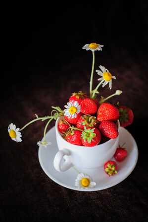 strawberry baskets: chamomiles and strawberries in white coffee cup, on dark brown