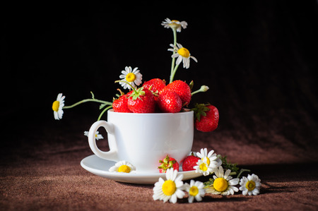 manzanillas y las fresas en blanco taza de caf�, en los rayos de la luz del sol, en el fondo de color marr�n oscuro photo