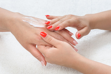 beauty salon, applying moisturizing cream onto the hands and massaging Stock Photo - 29267426