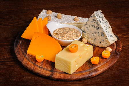 various cheeses with nuts and fruits on wooden plate photo
