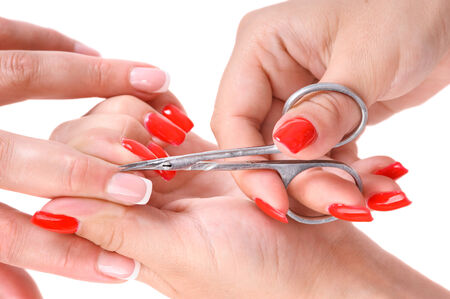 beauty salon, manicure applying, cutting the cuticle with scissors photo
