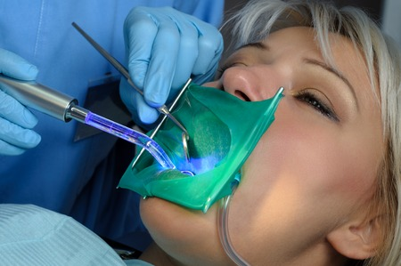 curing: dentist with patient, using dental curing light