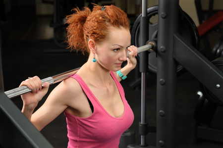 squats: young girl doing squats with barbell