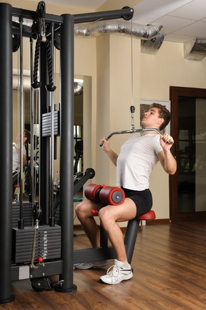 lats: young man doing lats pull-down workout