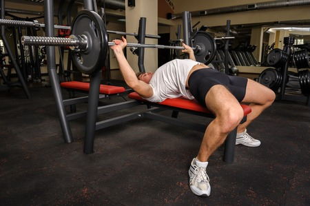 powerlifting: young man doing bench press workout in gym
