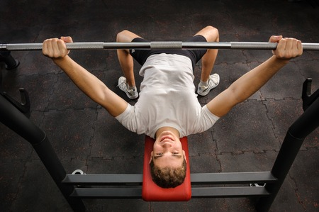 workout gym: young man doing bench press workout in gym