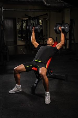 체육관에서 벤치 프레스 운동을하고있는 젊은 남자 스톡 콘텐츠