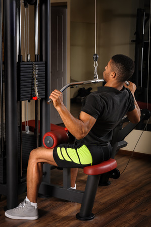 Young man doing lats pull-down workout Standard-Bild