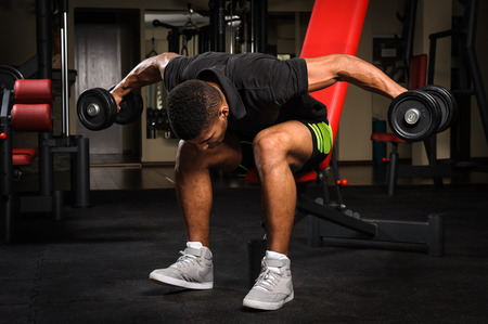 lats: Young man doing Seated Bent Over Dumbbell Reverse Fly workout in gym