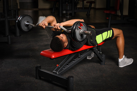 Young man doing arms bench french press workout in gym Stock Photo