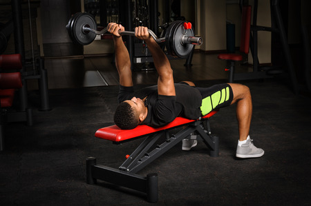 gym: Young man doing arms bench french press workout in gym Stock Photo