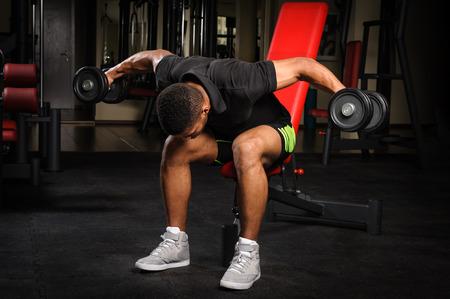 mosca: Hombre joven que hace sentado con mancuernas entrenamiento doblado Fly inversa en el gimnasio Foto de archivo