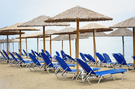 deck chairs: Reed umbrellas and deck chairs at the beach