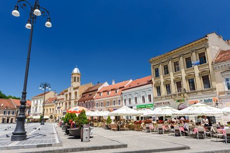 medieval: Brasov, Transylvania, Romania, 6th July 2015: Council Square is historical center of city, people walkinng and sitting at outdoor terraces and restaurants.