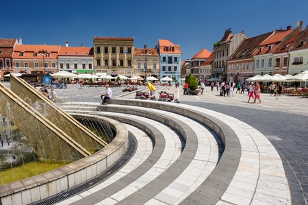city people: Brasov, Transylvania, Romania, 6th July 2015: Council Square is historical center of city, people walkinng and sitting at outdoor terraces and restaurants.