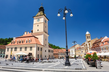 city centre: Brasov, Transylvania, Romania, 6th July 2015: Brasov Council Square is historical center of city, people walkinng and sitting at outdoor terraces and restaurants.
