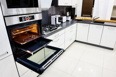 현대 럭셔리 하이 - 테크 검은 색과 흰색 부엌, 깨끗한 인테리어 디자인, 오픈 도어와 오븐에서 focu