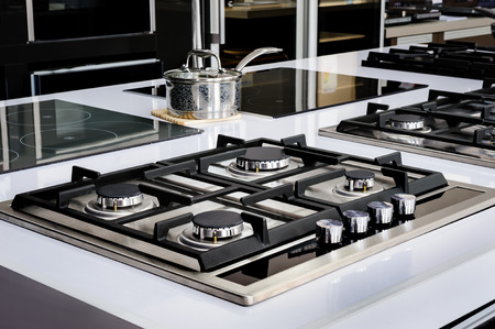 Brand new never used gas stove with stainless tray in appliance retail store Foto de archivo