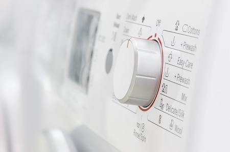 front loader: primer plano de la nueva ropa blanca o lavadora, foco selectivo en los elementos de control