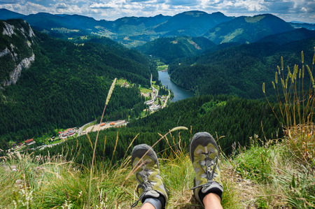 first day: Somebody is sitting at the edge of cliff in mountains, showing his feet wearing hiking shoes. First person shoot. Retezat area, Carpathians, Romania Stock Photo
