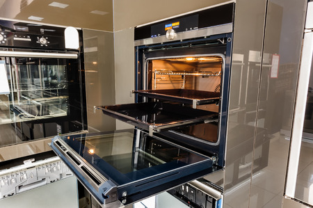 Modern luxury hi-tek black and white kitchen, clean interior design, focus at oven with open door 版權商用圖片