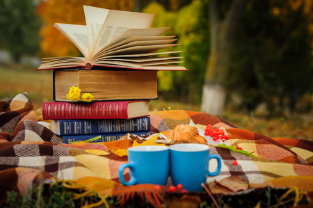 Romantic autumn still life with books, plaid, croissant, coffee cups and leaves Stock Photo