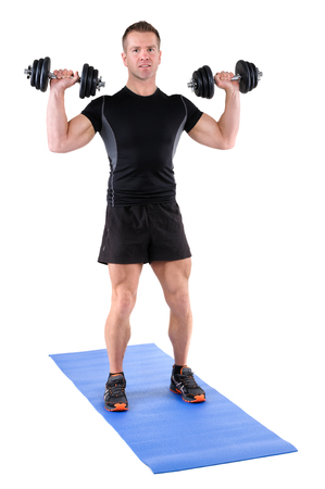 free weights: young man fitness instructor shows starting position of standing dumbbell shoulder press, isolated on white