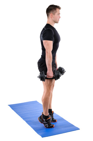 Young man shows finishing position of Standing Dumbbell Calf Raise with Dumbbels workout, isolated on white